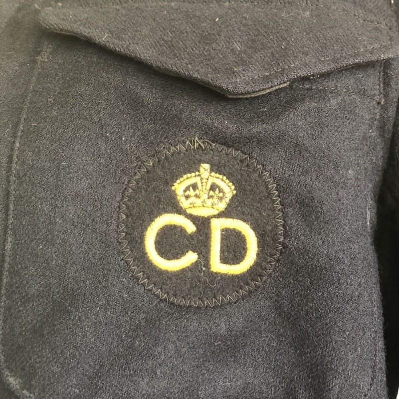 An original CD breast badge sewn to the left pocket of a battledress blouse.