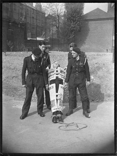 Four ARP wardens demonstrate the use of a Neil Robertson rescue stretcher.