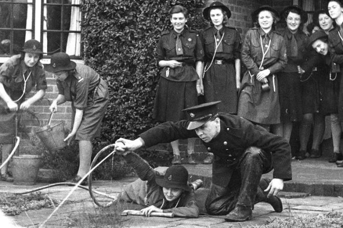 A fireman instructs Girl Guides in the use of a stirrup pump