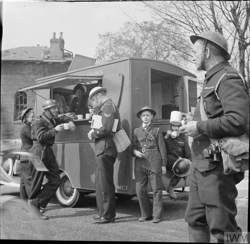 A group of wardens and messenger grab a quick cup of tea during am ARP training exercise in Fulham, London in 1942.
